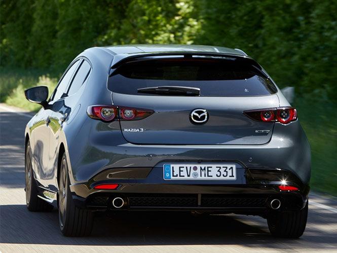 Mazda 3 in grau beim Fahren in der Heckansicht