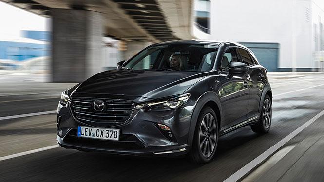 Mazda CX-3 in grau von schräg vorne in Fahrt