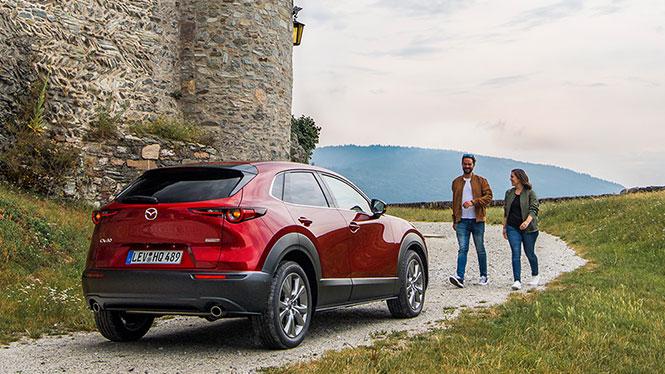 Mazda CX-30 Gebrauchtwagen in rot von schräg hinten mit zwei Personen davor