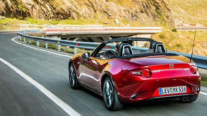 Mazda MX-5 Neuwagen in rot während der Fahrt von schräg hinten